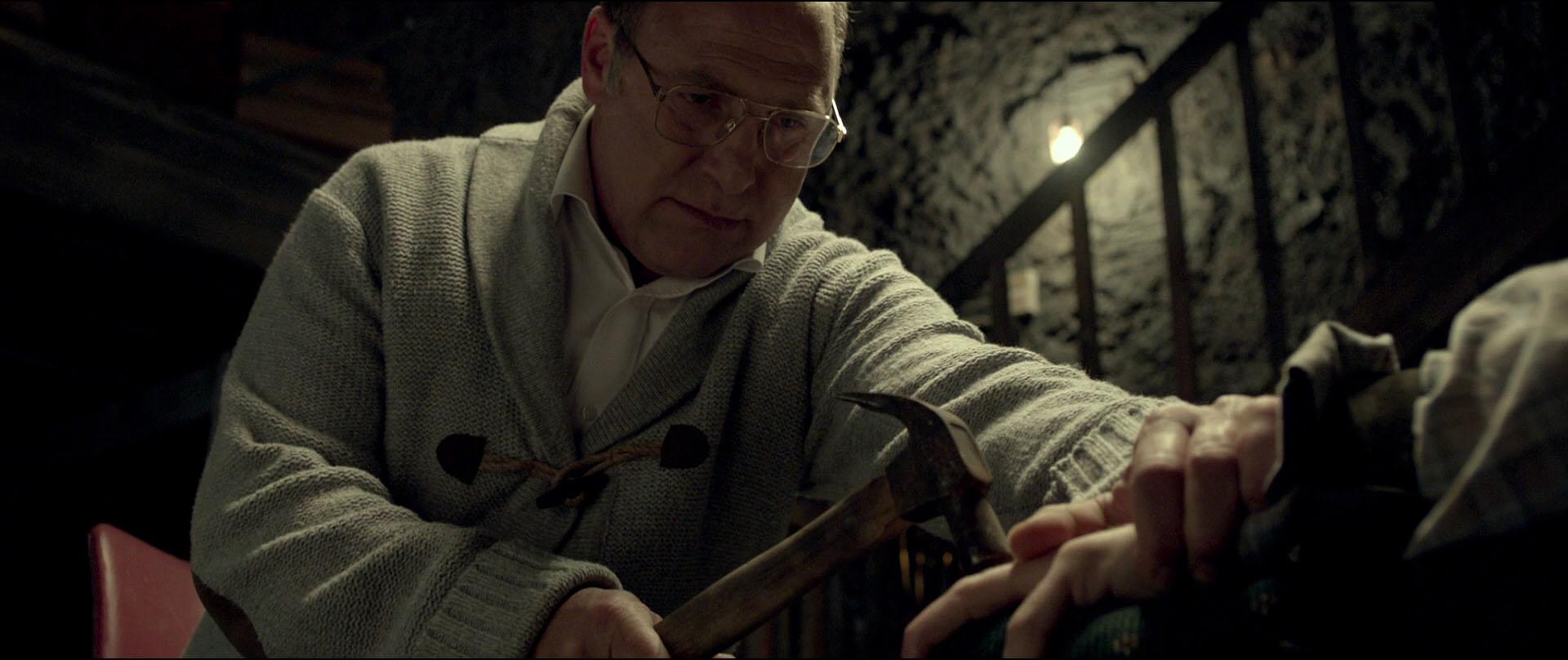Papá Venganza (Tzachi Grad) a punto de romper dedos a martillazos.